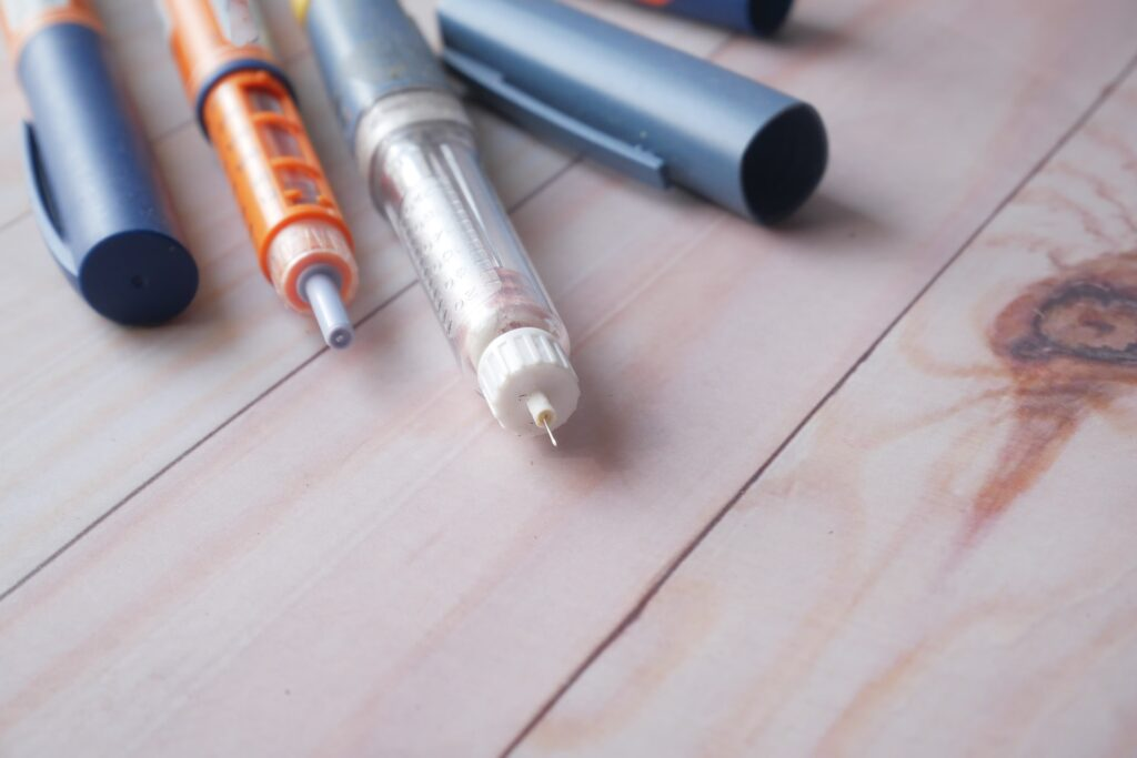 Insulin pens on wooden background
